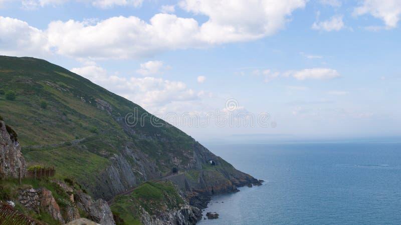 Co峭壁  威克洛,俯视爱尔兰海,当铁路隧道的爱尔兰被切开成山 图库摄影