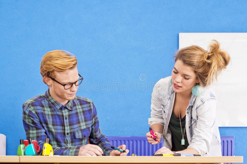 Co-design. Two designers at work, co-designing a product, with markers in various colors in a colorful office with a white board and a blue wall stock image