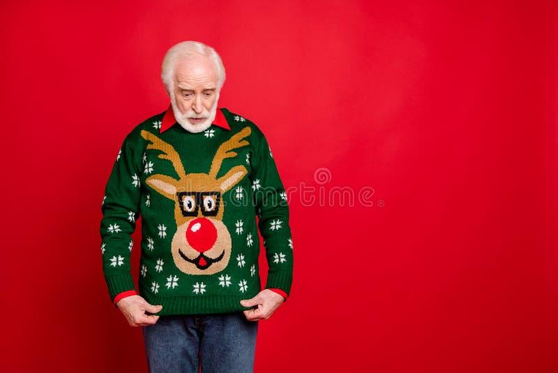 Co dostałem? Portret zdumionego staruszka spogląda na sweter z reniferami na imprezę o tematyce świątecznej zdjęcia stock
