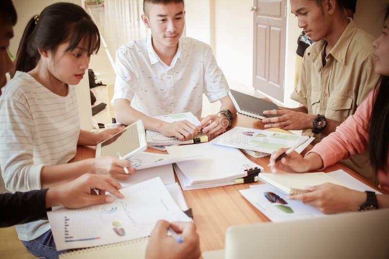Co-het werk het concept van de teamvergadering: Nieuwe Aziatische Genaration-Bedrijfsmensen die en gebruiks digitale tablet samen stock foto