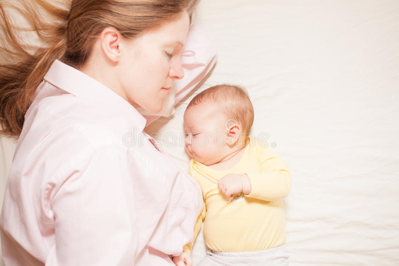 Co-sleeping mother and baby. Co-sleeping mother and three months baby after breastfeeding on the bed stock photo