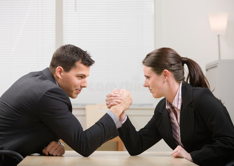 Co-workers arm wrestling for dominance. Co-workers aggressively arm wrestling for dominance stock photos