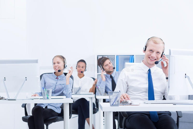 Co-workers in call center. Relaxed and focused co-workers are sitting at desk in call center stock images