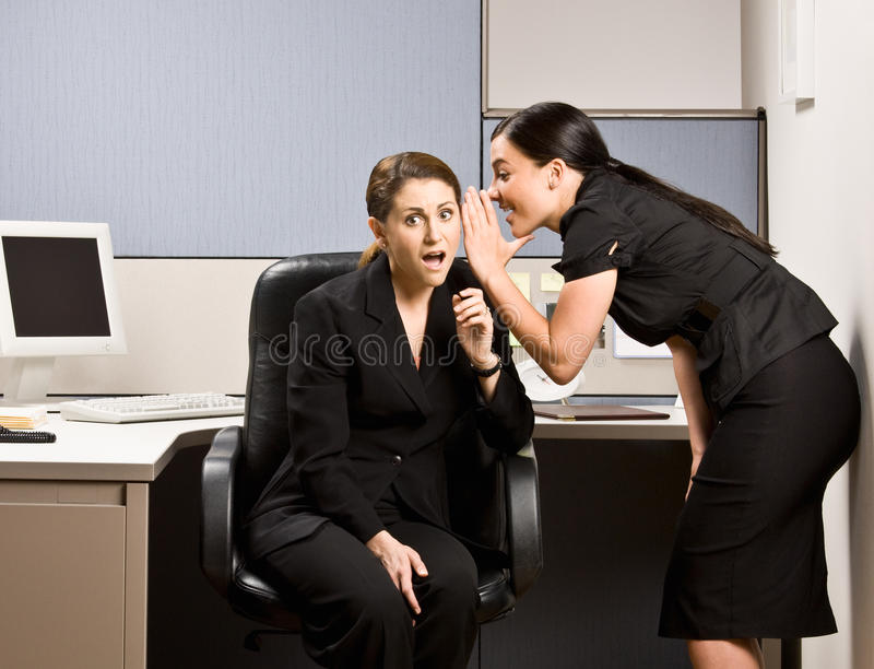 Co-workers gossiping. Two co-workers gossiping at the office stock photography