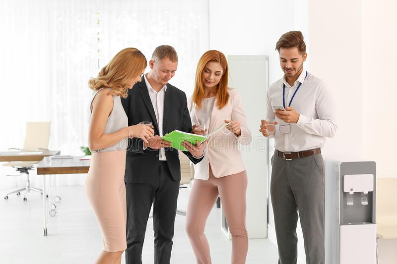Co-workers having meeting near water cooler. At workplace stock photos