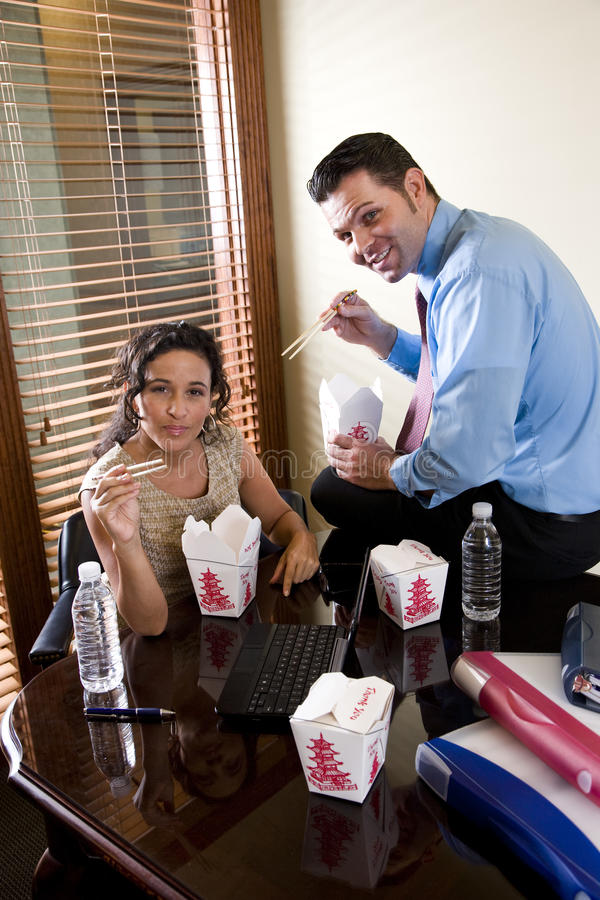 Co-workers in office eating Chinese takeout food. Office workers eating Chinese takeout food in boardroom while working on laptop stock photo