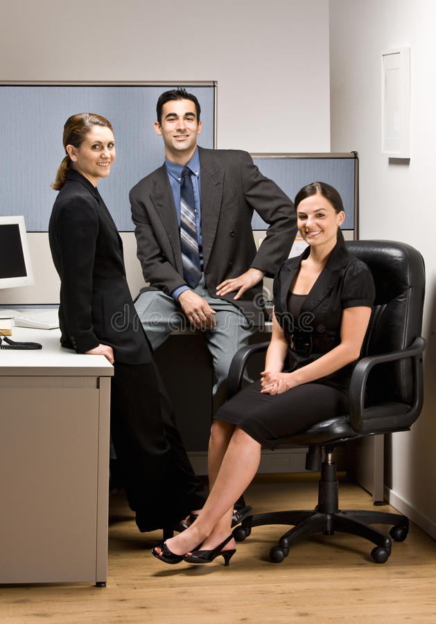 Co-workers sitting in office cubicle. Co-workers sitting in an office cubicle royalty free stock photos