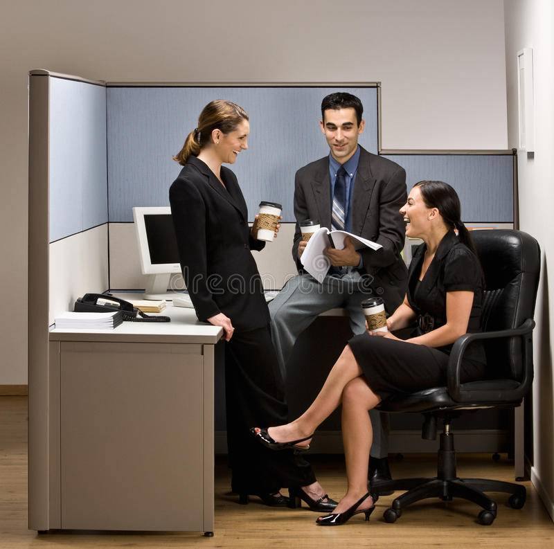 Co-workers talking in office cubicle. Co-workers talking in an office cubicle royalty free stock photo