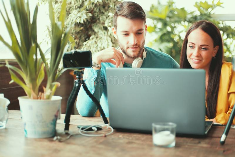 Co working young couple using laptop, smartphone on tripod, sitting at table video blogging together royalty free stock photography