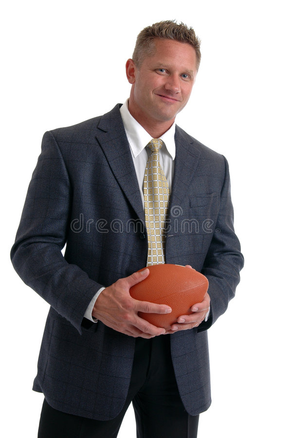 Coach. A muscular man in a suit holding a football