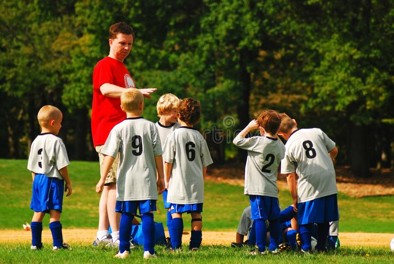 A coach assigns positions at a youth soccer game. A coach assigns positions to the children on his team at a youth soccer game royalty free stock image