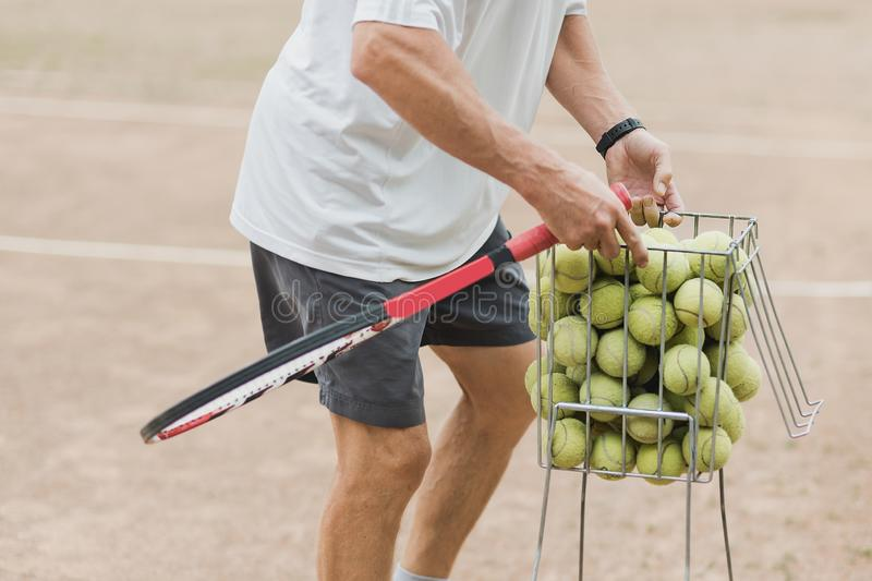 Coach collects tennis the balls in the basket after training. Tennis lesson. Court sport racquet lifestyle sunlight racket people outdoors play practice royalty free stock photography