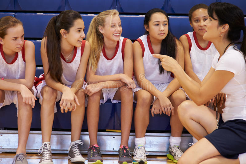 Coach Of Female High School Basketball Team Gives Team Talk. In Gymnasium Kneeling Down stock photography