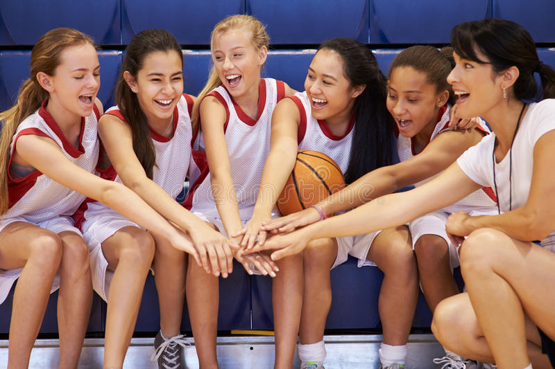 Coach Of Female High School Basketball Team Gives Team Talk. Whilst Everyone Puts Hand In The Middle Smiling royalty free stock photo