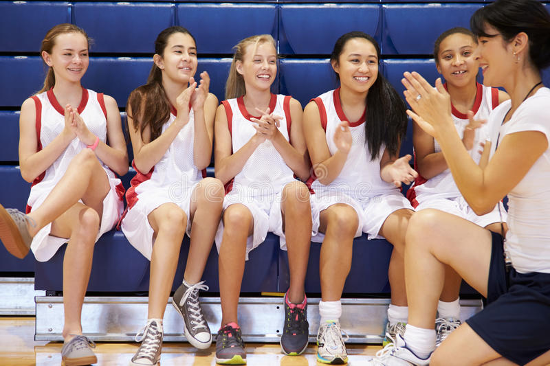 Coach Of Female High School Basketball Team Gives Team Talk. Whilst Sitting On Bench Clapping stock photos