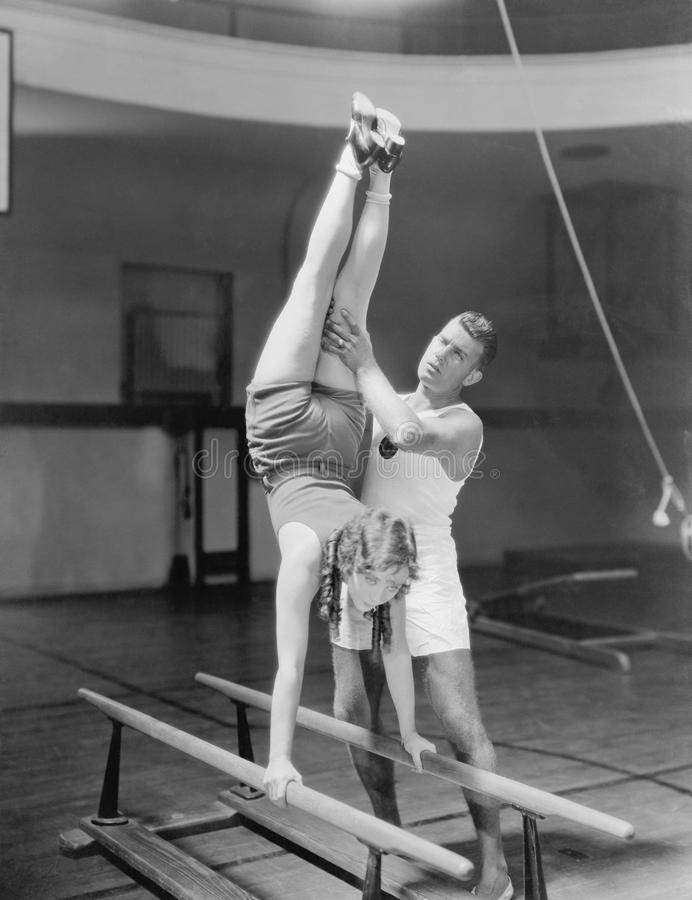Coach helping woman on parallel bars stock images