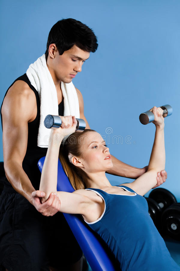 Coach Helps Woman To Exercise With Weights Royalty Free Stock Image