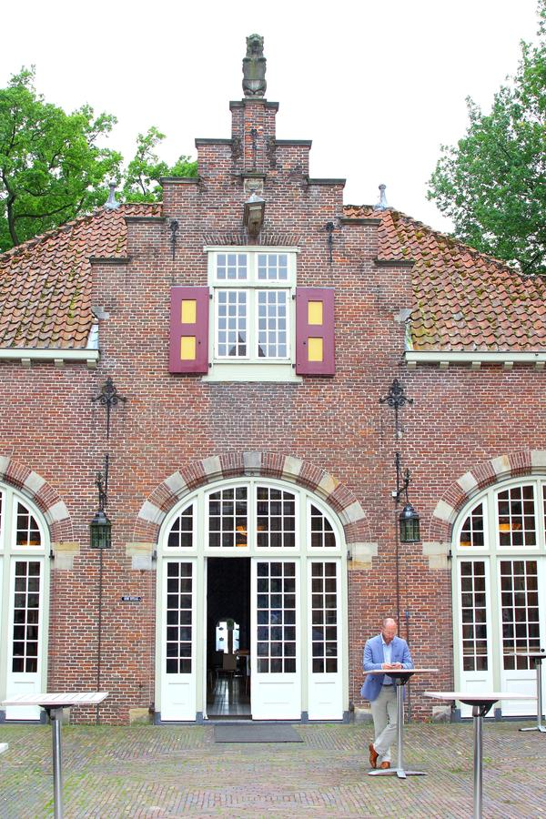 Coach house Nyenrode Business University, Netherlands. Man is looking at his mobile phone in front of the coach house of castle Nyenrode and private Business royalty free stock photography
