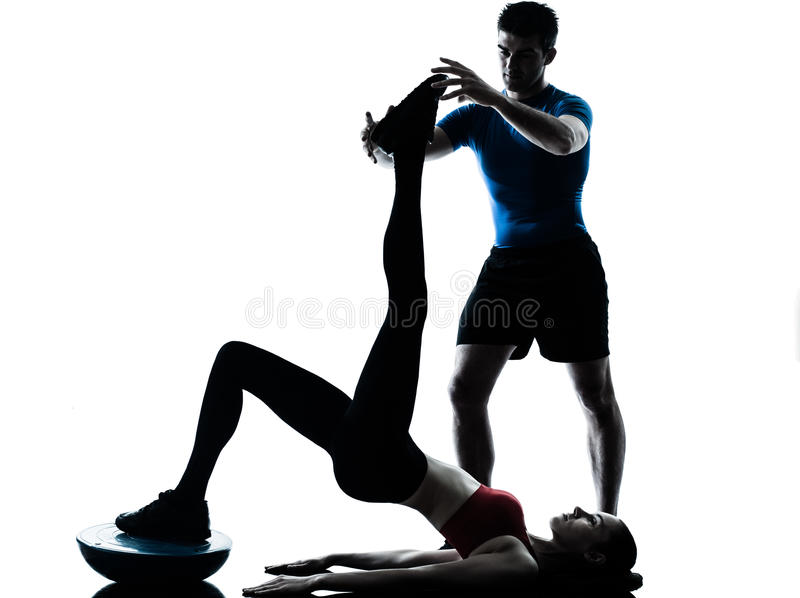 Coach man woman exercising abdominals with bosu royalty free stock image
