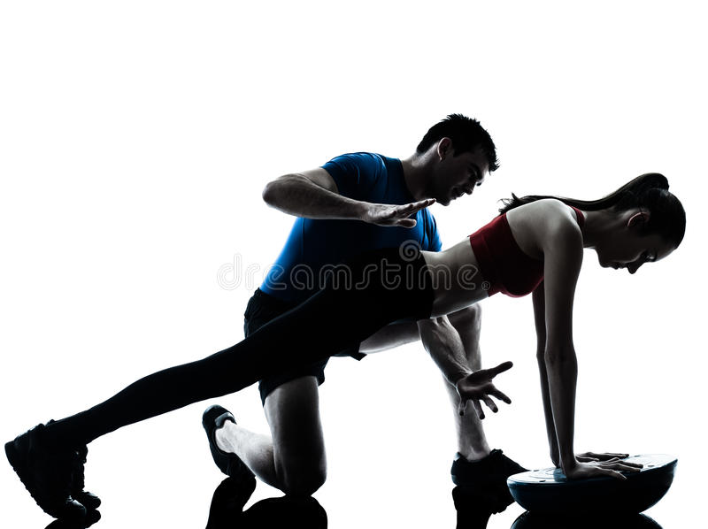 Coach man woman exercising abdominals with bosu silhouette royalty free stock photos