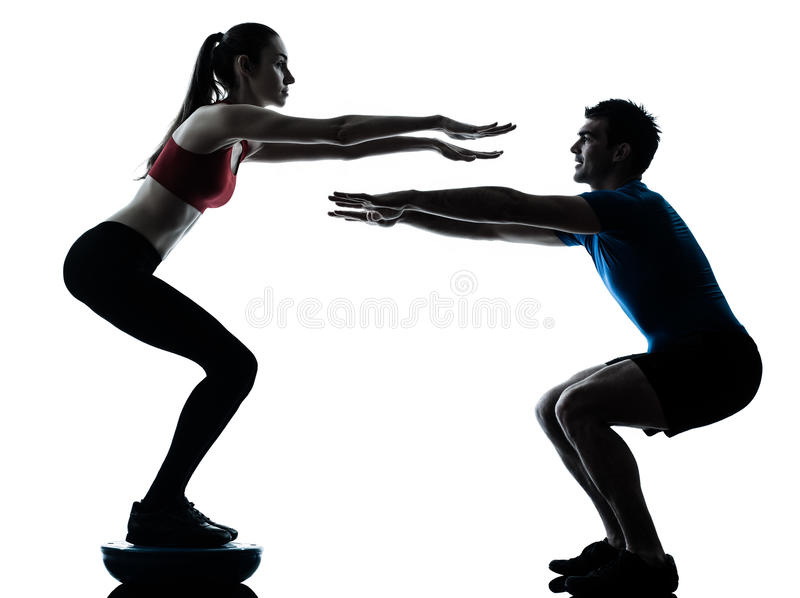 Coach man woman exercising squats on bosu stock images