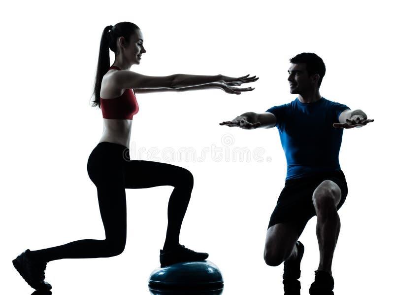 Coach man woman exercising squats on bosu royalty free stock photo