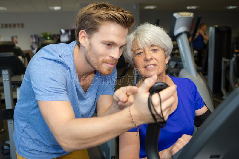 Coach showing old woman exercise result stock photography