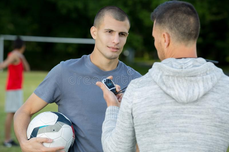 Coach with stopwatch talking to young male player royalty free stock photo