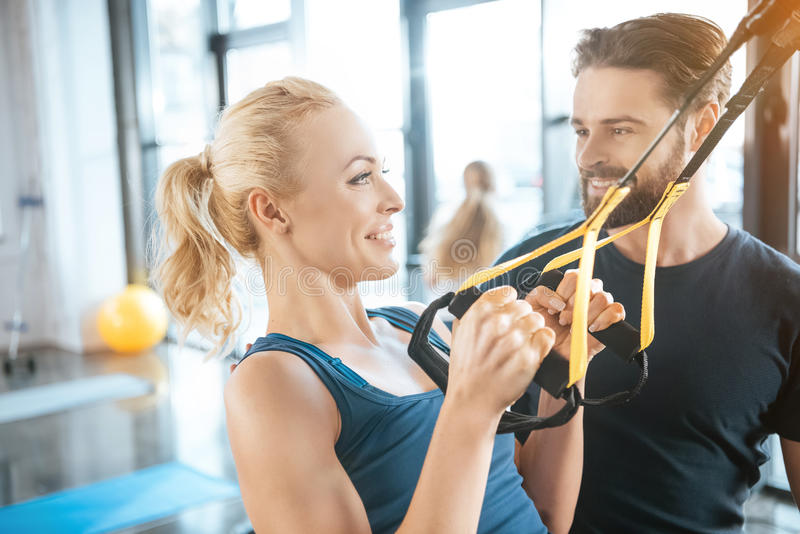 Coach talking with blonde fitness woman training with trx fitness straps. Coach talking with blonde fitness women training with trx fitness straps in gym stock photo