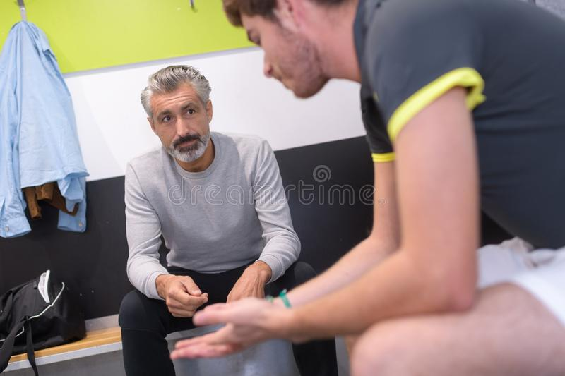 Coach talking to disappointed sportsman in changing rooms. Sport royalty free stock images