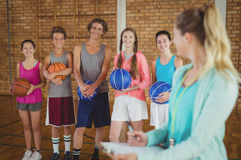 Coach talking to high school kids in basketball court royalty free stock photography