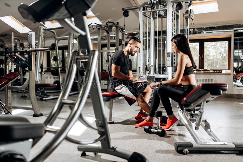 Coach talks with athletic girl dressed in black sport clothes sitting on the bench in the gym stock photo