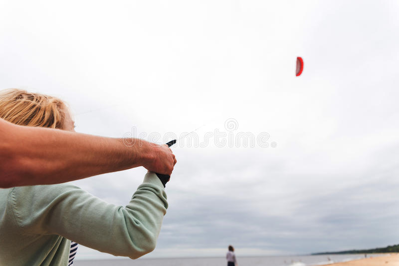 Coach teaches girl control the kite. On the seashore stock image