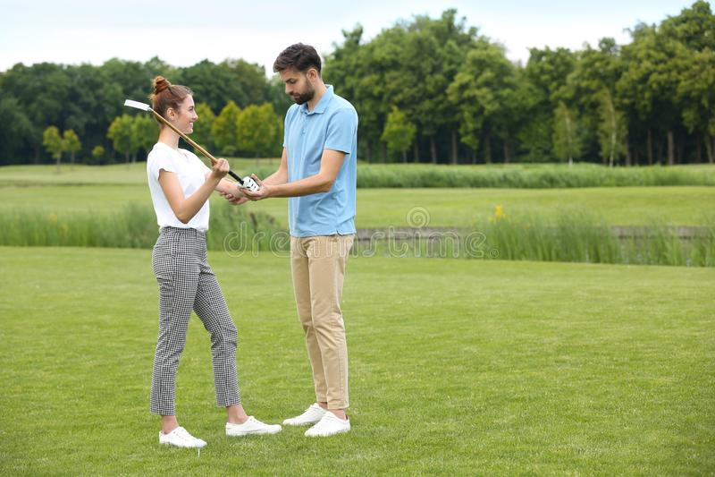 Coach teaching woman to play golf on course stock photos