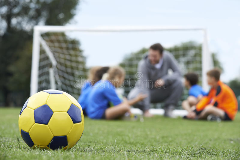 Coach And Team Discussing Soccer Tactics With Ball In Foregroun royalty free stock photography