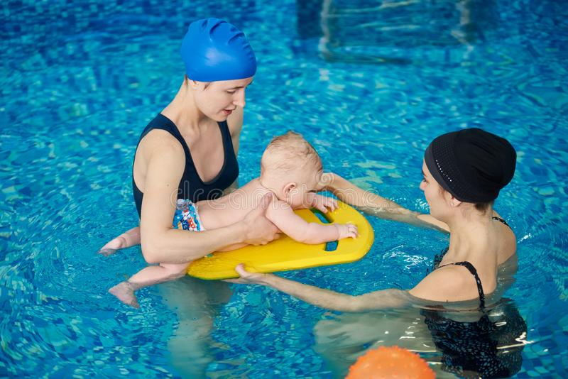 Coach training newborn child floating at swimming courses mom and baby. Women focusing on little child on swimming board stock photo