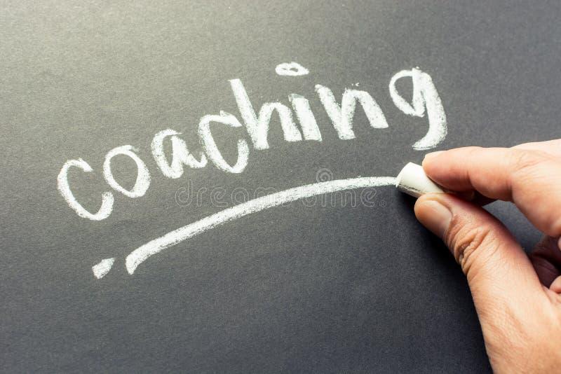 Coaching. Hand writing Coaching topic on chalkboard stock images