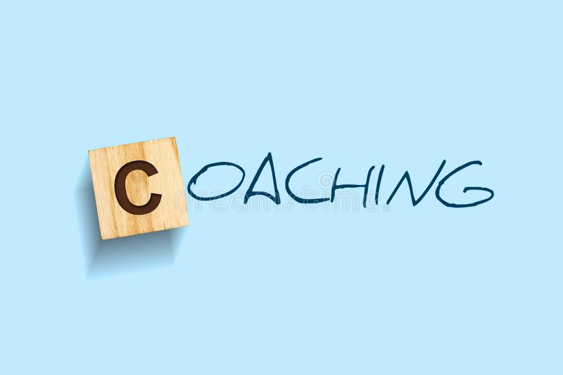 Coaching. Words written on a wooden block. Blue background. Isolated. Business or education concept stock photo
