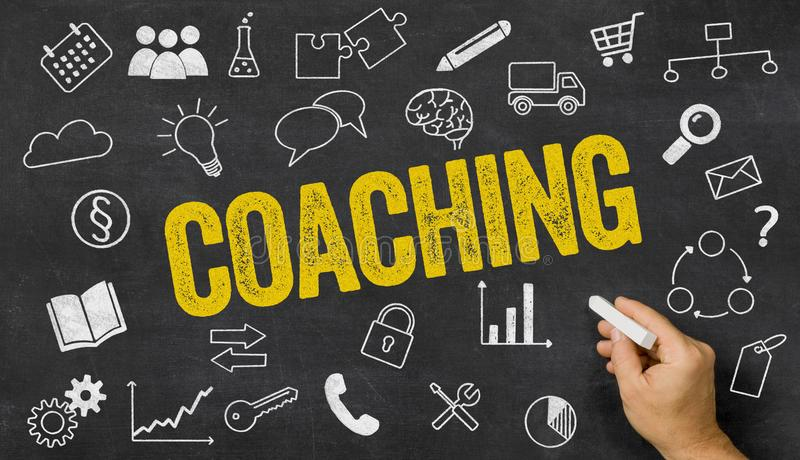 Coaching written on a blackboard. With icons royalty free stock image