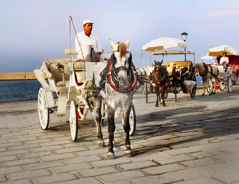 Coachman Horse Carriage Ride. Coachman sitting in a horse-drawn carriage waiting for tourists in Chania port. Crete island Greece stock photography