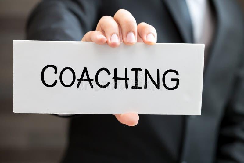 Coachning, meddelande på det vita kortet och håll av affärsmannen arkivbild