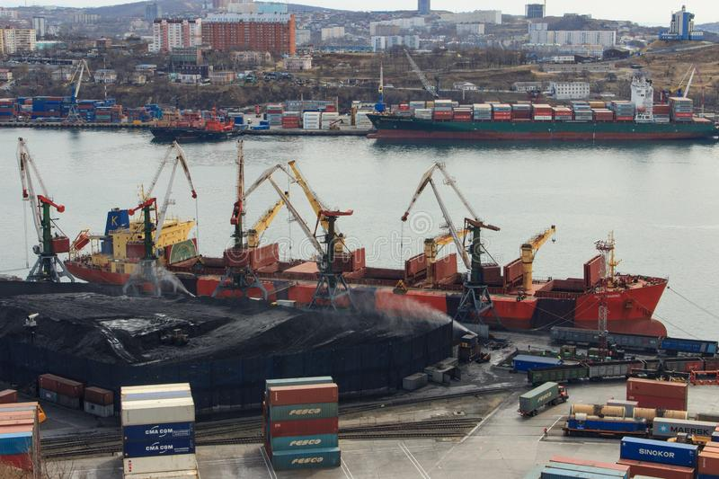 Coal loading onto a bulk carrier in an open way at a coal terminal in the port of Vladivostok stock photography