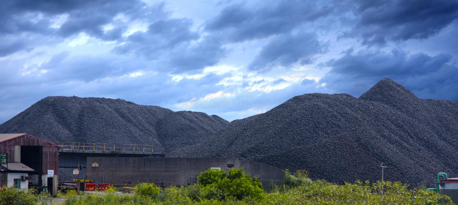 Coal mine. With stormy sky and bushes in foreground royalty free stock photo