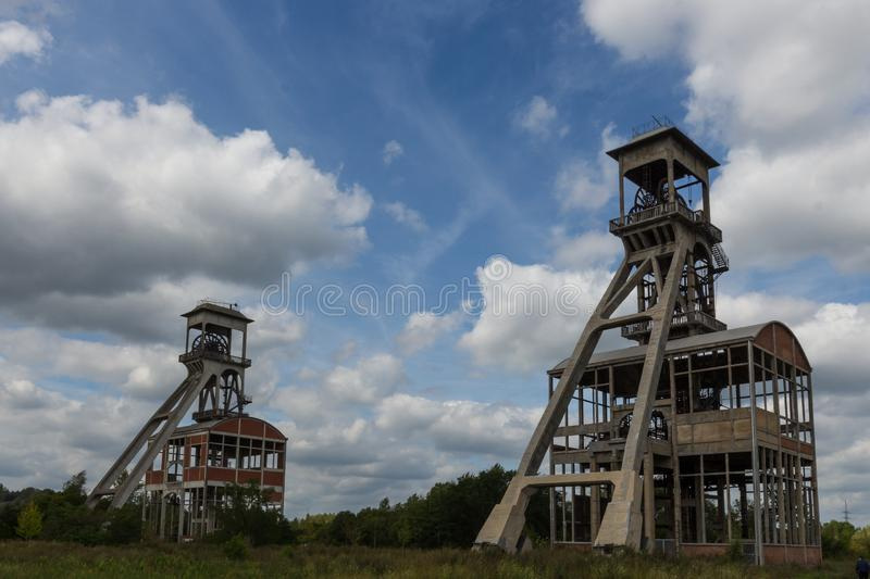 For coal mine elevators under a dramatic sky near Maasmechelen Village. A dramatic sky with former elevator shaft for the coal mines in Maasmechelen, Belgium royalty free stock photo
