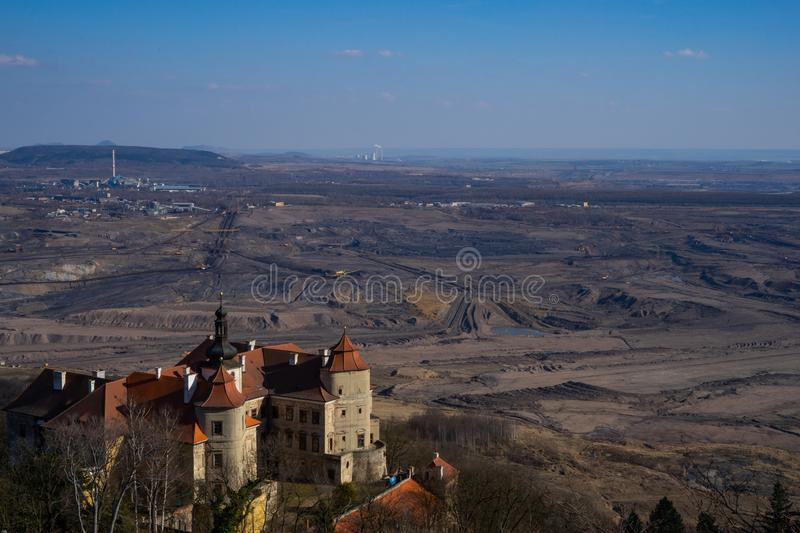 Coal mining contrast. View of the devastated landscape of coal mining. Contrast with the historic castle of Jezeří, which stands alone on a hill above the royalty free stock photo