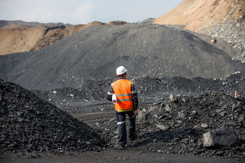 Coal mining in an open pit. Worker is looking on the huge open pit royalty free stock images