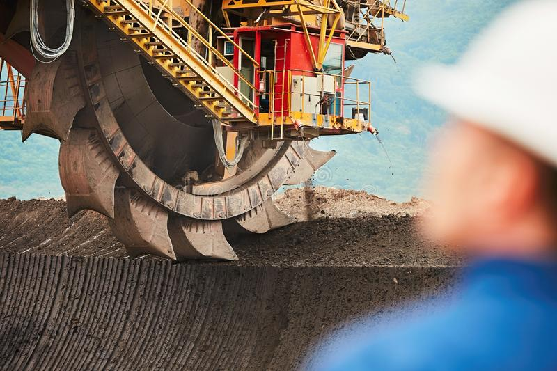Coal mining in an open pit. Worker is looking on the huge excavator - industry in Czech Republic stock photography