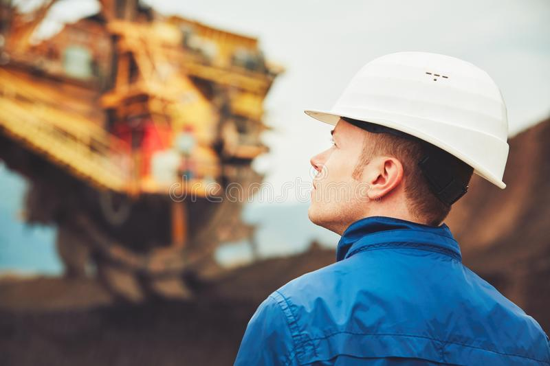Coal mining in an open pit. Worker is looking on the huge excavator - industry in Czech Republic royalty free stock image
