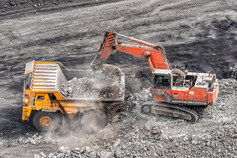 Coal mining in a quarry. A hydraulic excavator loads a dump truck. royalty free stock photos
