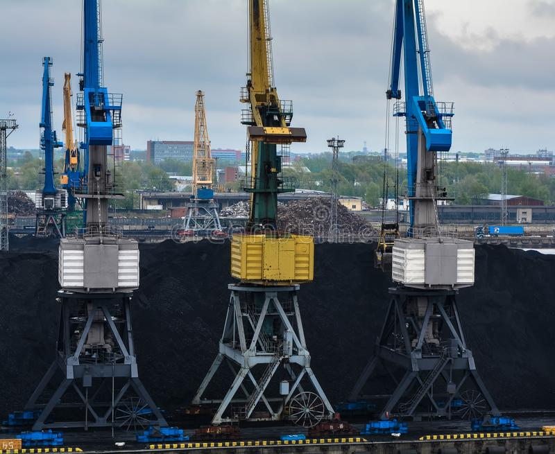 Coal industry. Coal pile is being loaded by several colorful cranes royalty free stock photos